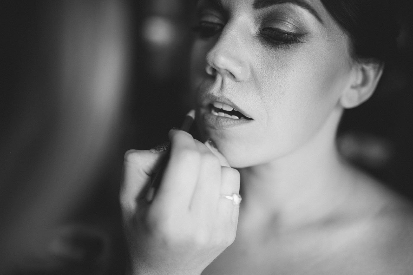 Black and white close up of bride having her lipstick applied