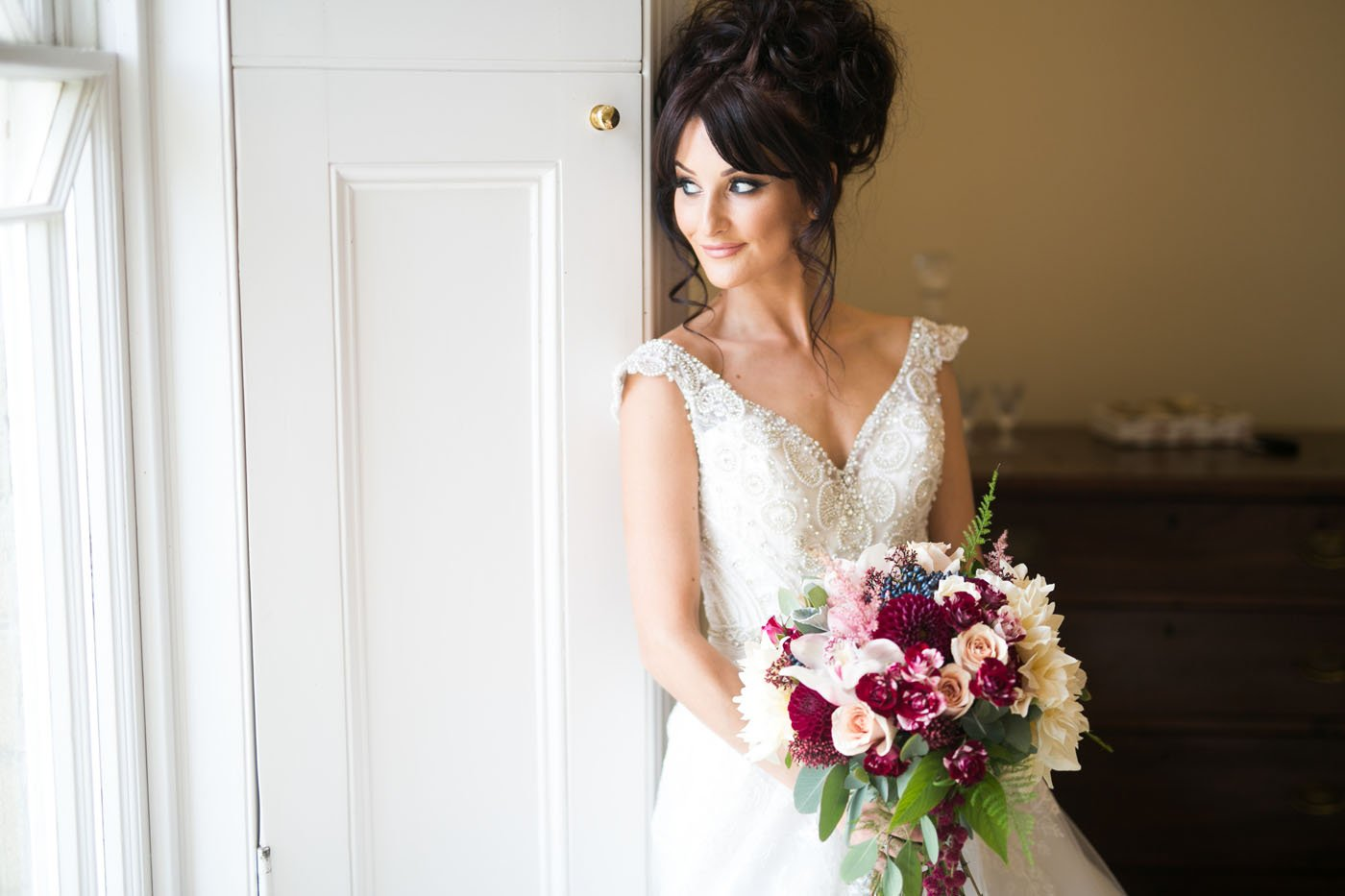 Bride looks out the window holding her red and white bouquet at St Tewdrics