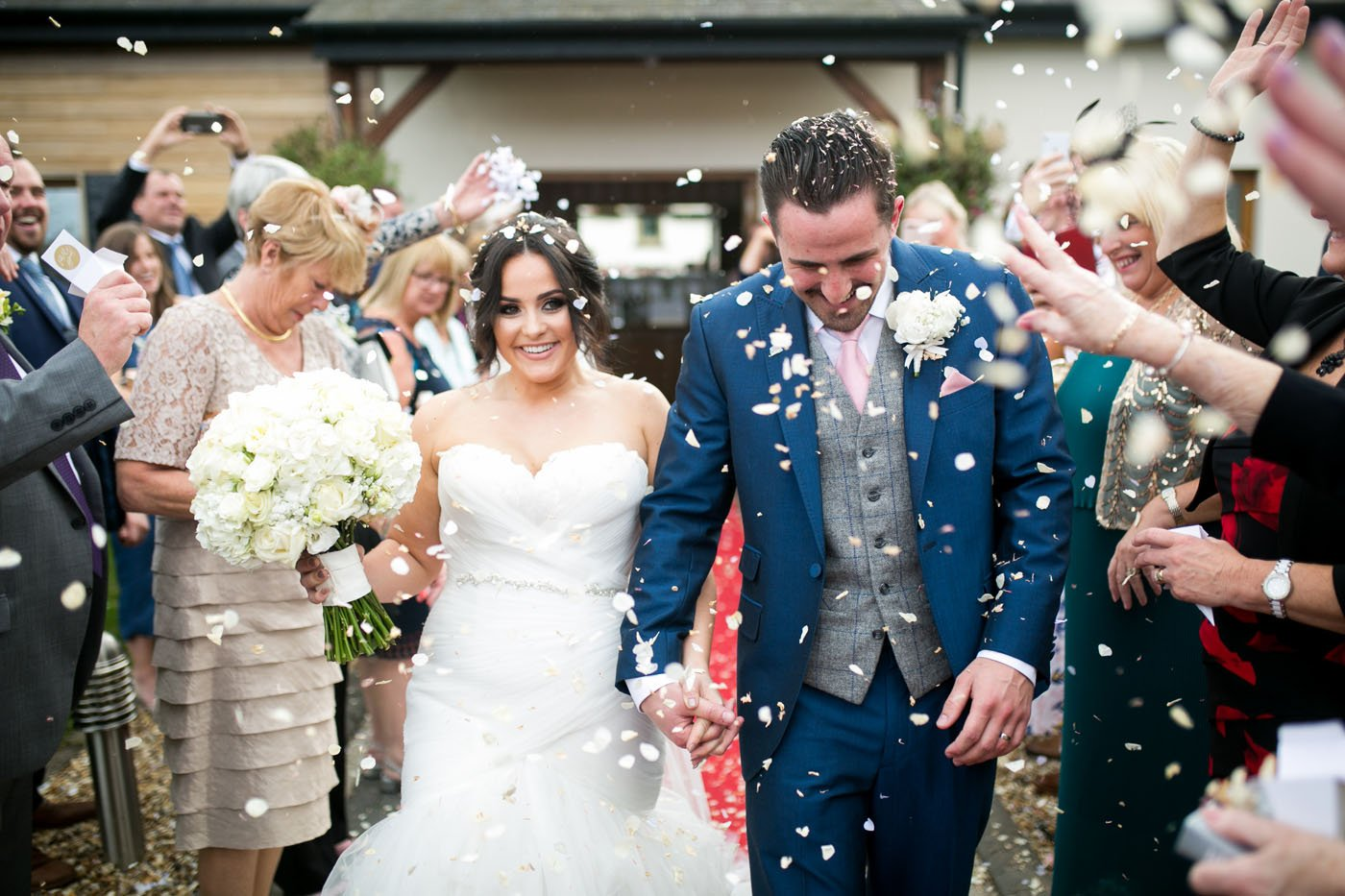 A bride and groom walk past their guests smiling as confetti is thrown on them