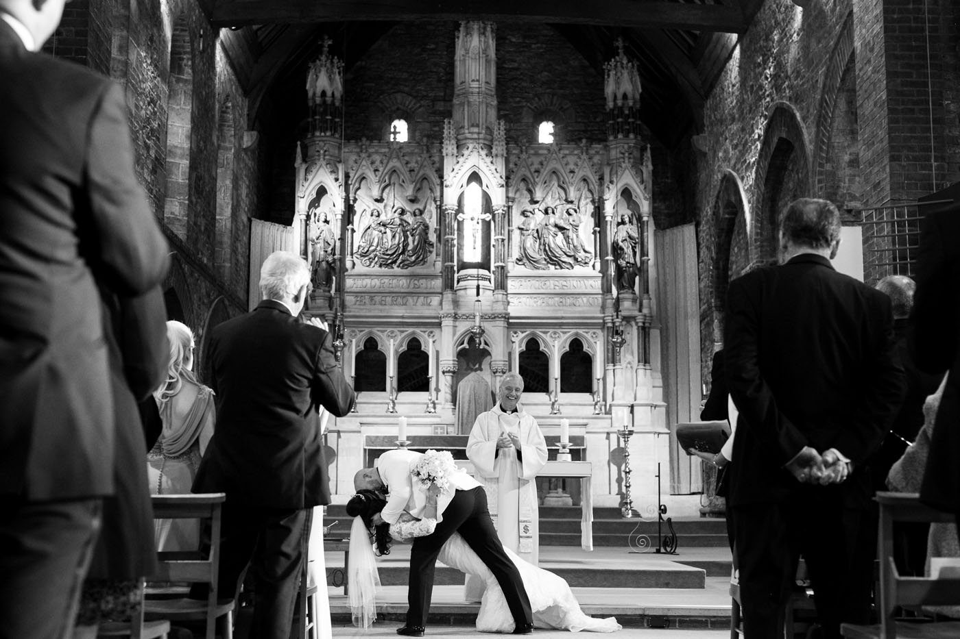 At the alter, a groom lowers his bride for a kiss