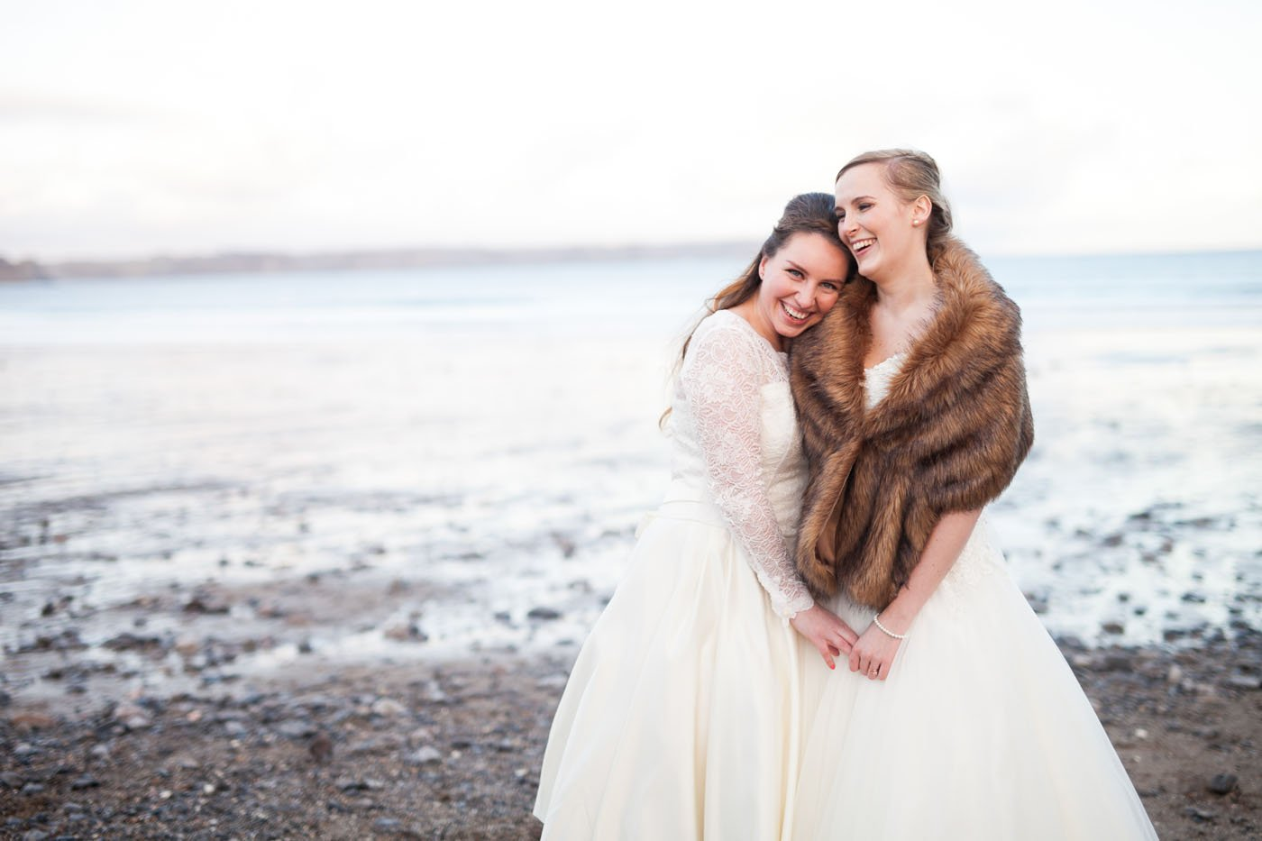 Two brides hug on the beech at Oxwich Bay