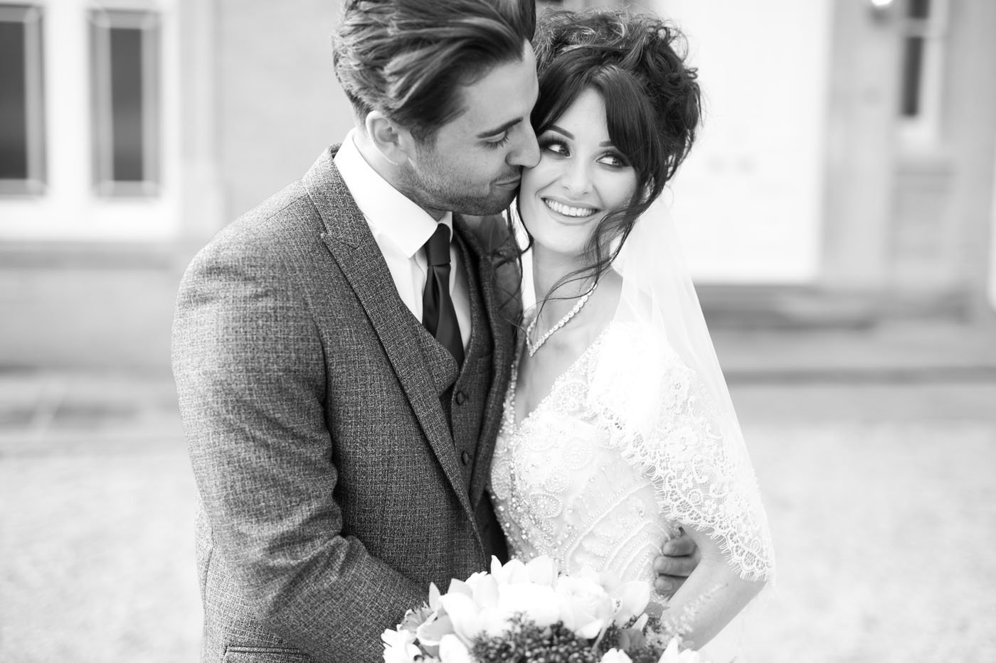 A groom kisses his brie on the cheek at St Tewcrics