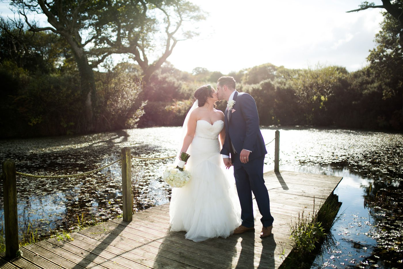 Standing on a pier at Oldwalls, a bride and groom kiss whilst the sun sets behind them