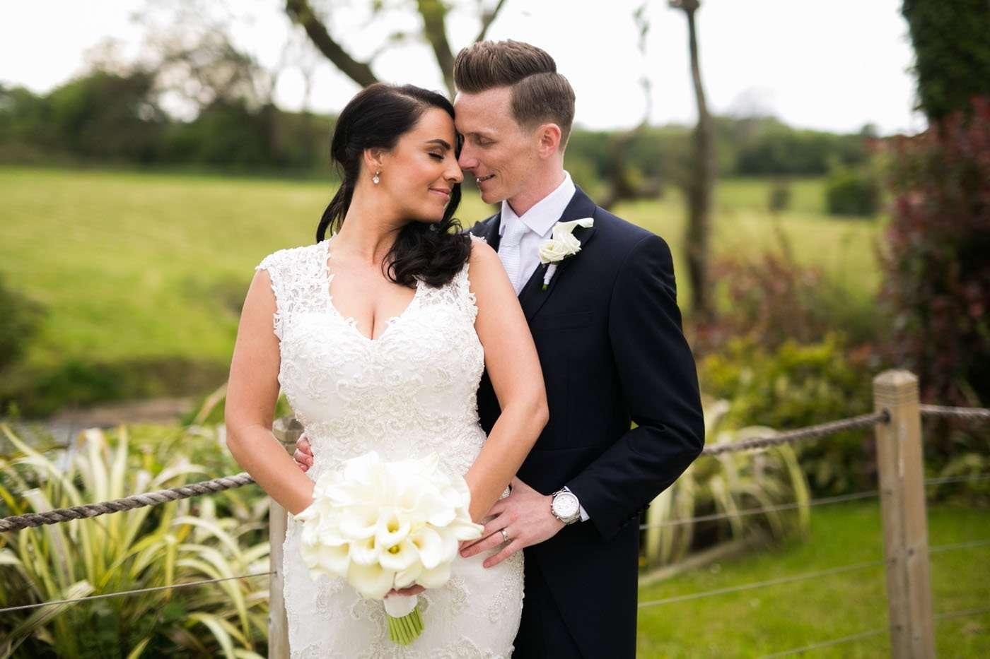 A groom hugs his bride from behind at Oldwalls