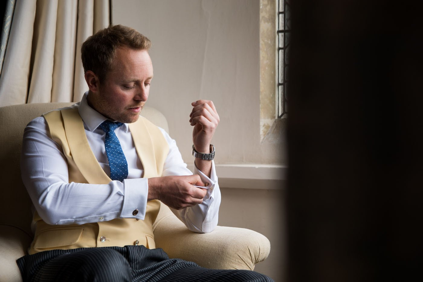Groom in a mustard waistcoat and blue tie buttons up his cufflinks