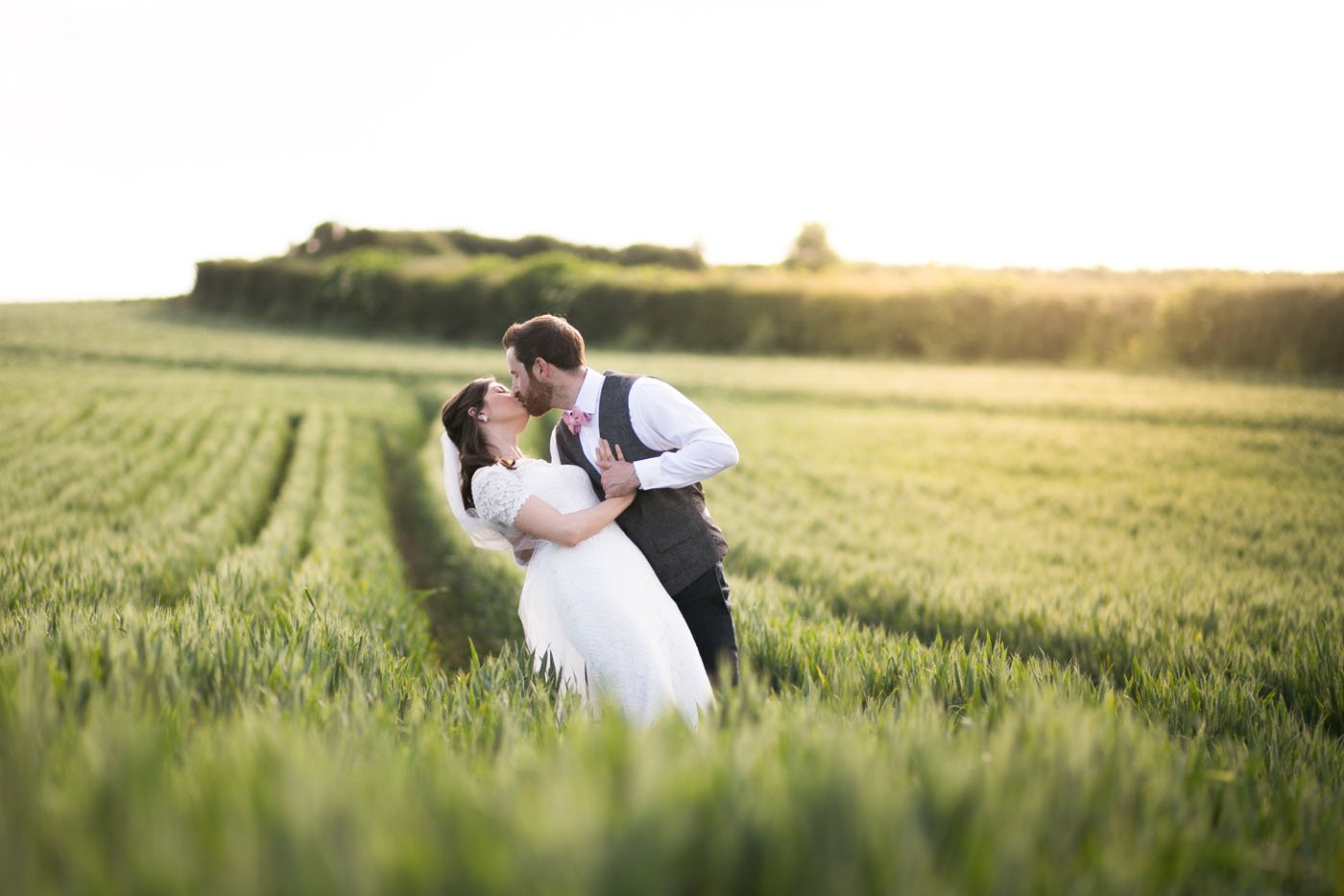 A bride is being lowered for a kiss by her groom in a green field