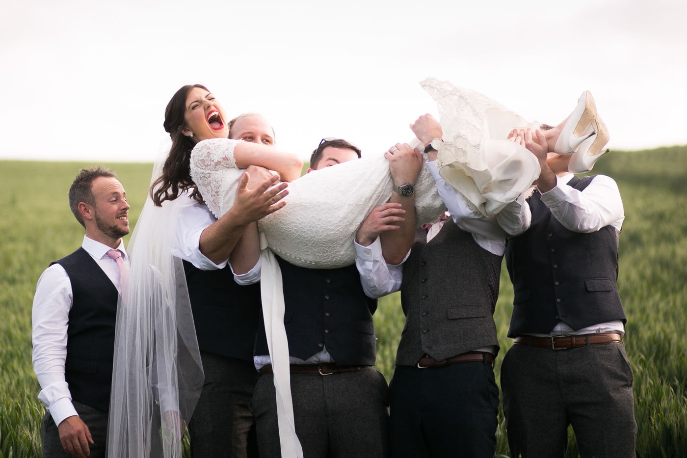 Bride is laughing while being picked up by the ushers