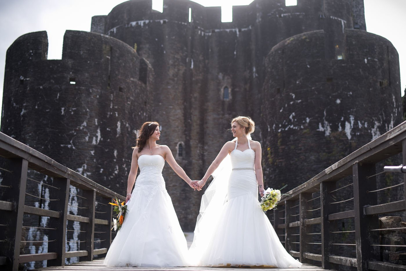 Two brides stand on a bride holding hands at Caerphilly Castle