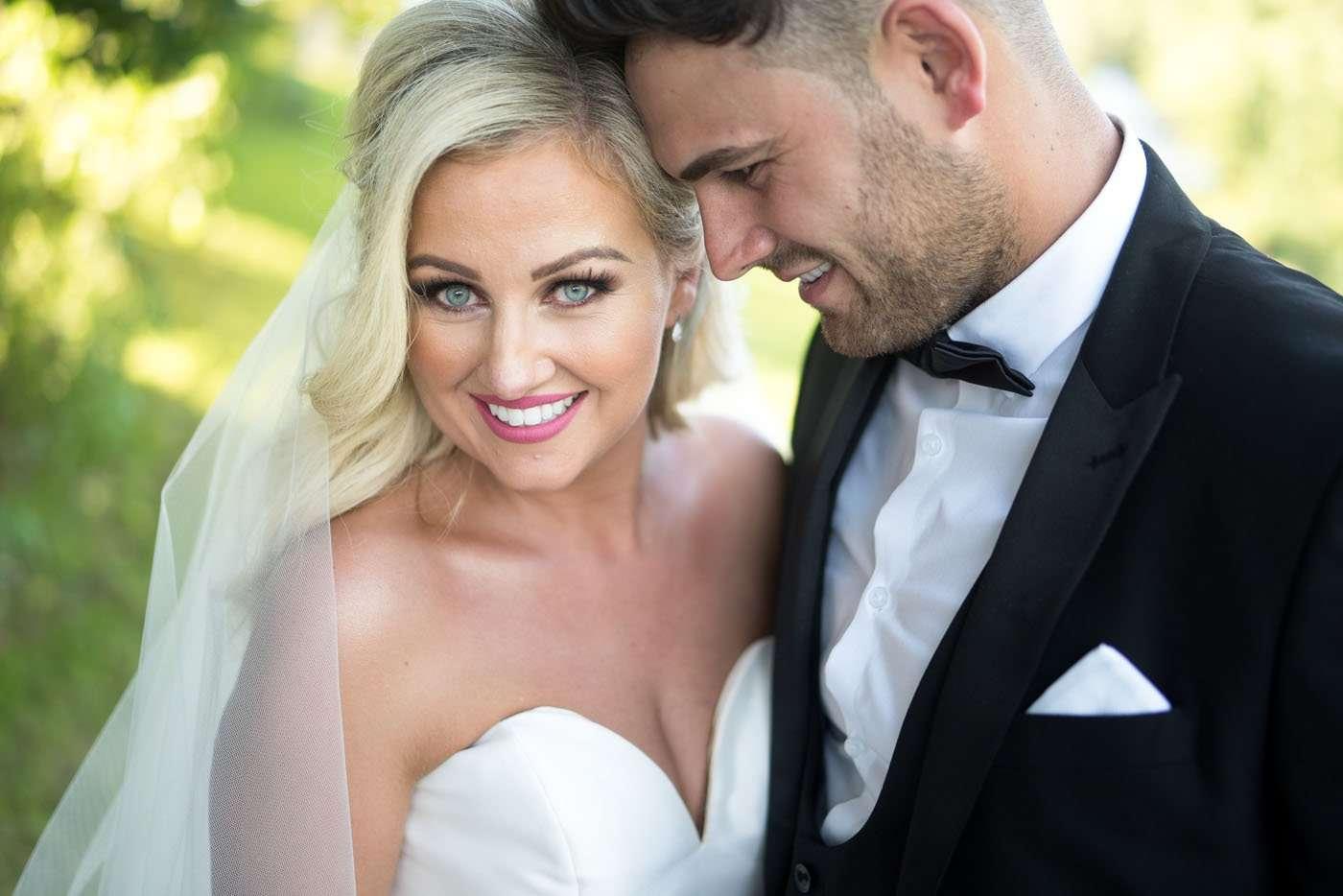 Bride and groom hug and smile at Canada Lodge and Lake